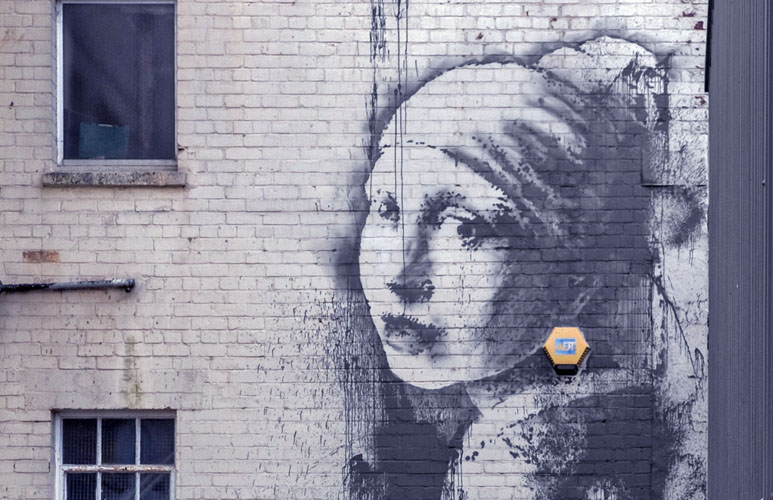 20 Oct 2014, Bristol, England, UK --- Bristol, United Kingdom. 20th October 2014 -- The new Banksy piece, 'Girl with a Pearl Earring' is see on a wall in Bristol Harbourside. -- A new piece from Banksy was left on a wall in his home town of Bristol depicting the painting 'Girl with a Pearl Earring' by Dutch painter Johannes Vermeer. The painting incorporates an alarm box as the model's earring. --- Image by © Paul Green/Demotix/Corbis